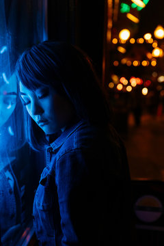 Young woman leaning against storefront under neon lights
