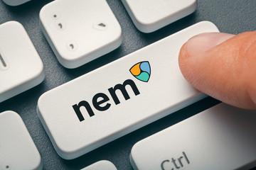 finger pressing computer key with nem coin logo. crypto mining concept