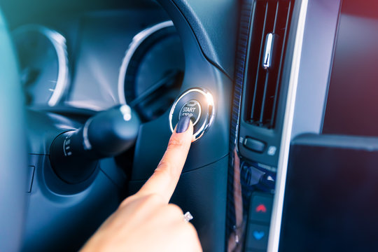 Woman driver pushing a start ignition button in the car
