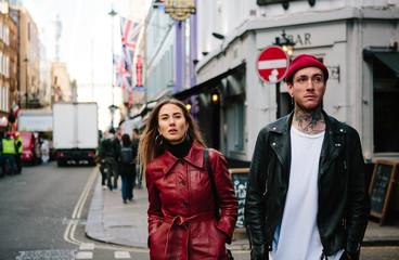 Cool couple wearing leather jackets out in the city.