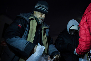 People receive food from the New York City's Coalition for the Homeless as they deliver food, donated clothing and supplies during winter storm Grayson in New York
