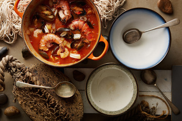 Seafood stew served in bowls in a rustic table setting.