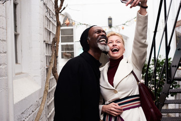Laughing couple taking self-portrait on mobile phone.