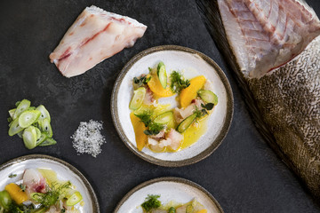 Three ceramic plates with raw fish, celery, orange and dill