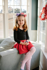 Beautiful young girl dressed up sitting on a chair