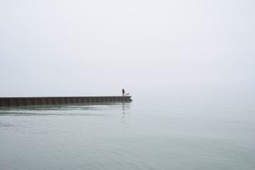 Woman and Dog on Foggy Lake