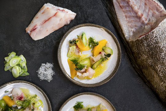 Three ceramic plates with raw fish, celery, orange and dill