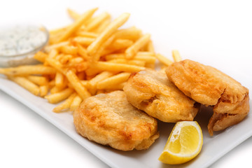 fish and chips with lemon and sauce on white plate