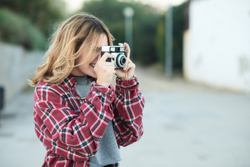 Smiling girl taking shot with film camera.
