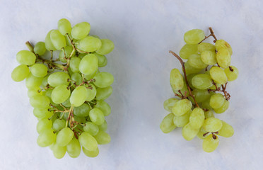 Green grapes, two bunches of grapes - fresh and dried, contrast, healthy food, grapes on a white background, wooden background, minimalism, pop art, retro style, berries, natural pattern