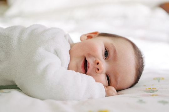 Smiling baby boy lying on the bed