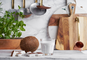 Whole coconut,raw coconut chunks and coconut cream on a kitchen work surface.