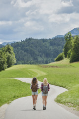 Traveler girl friends walking countryside road on wanderlust adv