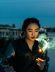 Young woman with sparkler firework in hand on rooftop at dusk