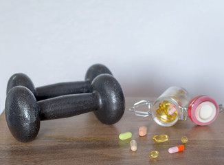 Muscle building with supplements with dumbbell on wooden background against white wall