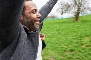 Smiling man with arms raised in park.