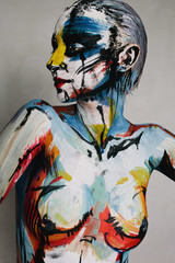 Emotive portrait of a young woman with colorful make-up and bodyart