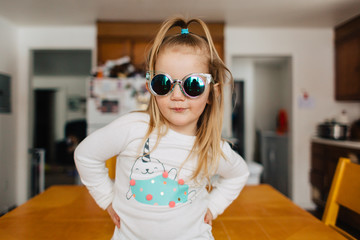 Cute toddler girl in narwhal shirt and funky sunglasses.