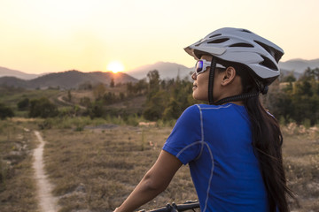 Female mountain biker looking at sunset view