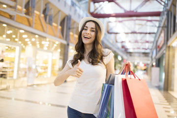 Attractive trendy woman in hat with shopping bags stands at shop. Modern caucasian girl with purchasing bags in big mall