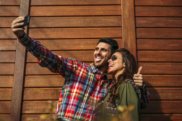 Handsome man and woman in wooden cabin with mobile phone.