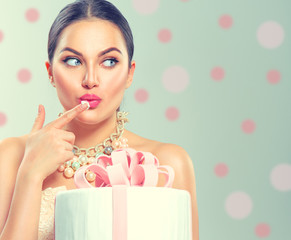 Funny joyful beauty model girl holding big beautiful party or birthday cake over green background and tasting it