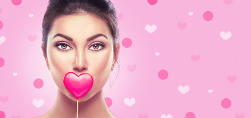 Valentine's Day. Beauty young fashion model girl with Valentine heart shaped cookie over pink background
