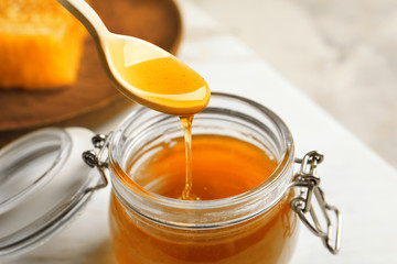 Honey pouring from wooden spoon into glass jar, closeup