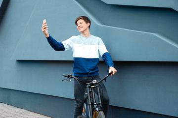 Hipster teenager with bicycle taking selfie near wall outdoors
