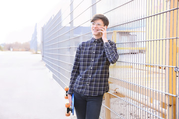 Hipster teenager talking on phone near fence outdoors