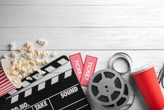 Tasty popcorn, movie reel, tickets and clapboard on wooden background