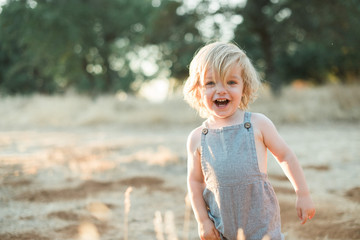 Toddler Boy Smiling in Old Fashioned Romper in Field