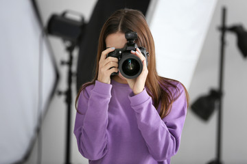 Beautiful young photographer taking photo in professional studio