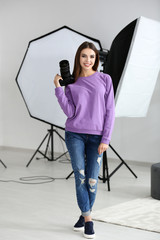 Beautiful young photographer with camera in professional studio