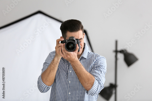Young Photographer Taking Photo In Professional Studio