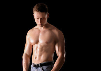 Muscular young bodybuilder on dark background