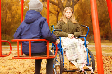 Sad little girl in wheelchair and boy on playground