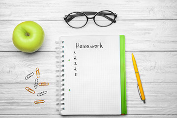 """Notebook with word """"Homework"""", apple and stationery on wooden background, top view"""