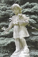 Vintage image of a sad angel on a cemetery. Weathered angelic cherub sculpture with broken wings. Angel guardian.