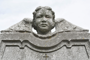 Vintage image of a sad angel on a cemetery. Weathered angelic cherub sculpture with wings. Angel guardian.