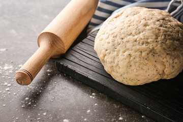 Wooden board with ball of raw dough and rolling pin on table