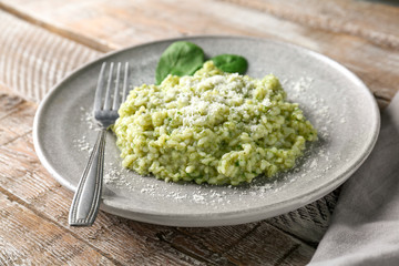 Plate with tasty spinach risotto on table, closeup