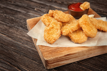 Wooden board with tasty chicken nuggets and sauce on table
