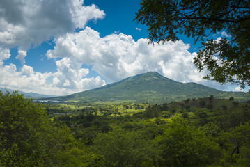 Summer landscape with mountains, cloudy sky, green grass and trees in Guatemala.