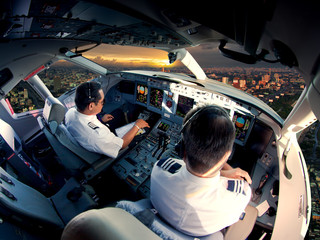 Cockpit of modern passenger jet aircraft. Pilots at work. Aerial view of modern city business district and sunset sky.