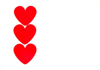 vertical row of 3 bright red hearts for Valentine's Day isolated on white