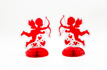 2 bright red cupid decorations facing one another  with hearts isolated on a solid background