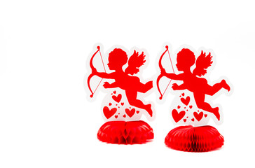 2 bright red cupid decorations with hearts facing left isolated on a solid background
