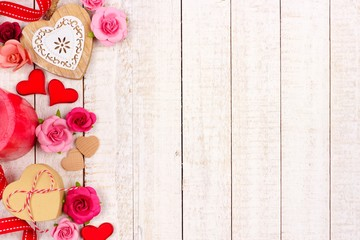 Valentines Day side border of hearts, flowers, gifts and decor against a rustic white wood background with copy space.