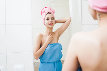 girl with a towel on her head examining herself in the mirror